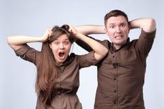 Сотрясены женщина и человек в коричневых одеждах, изумленный, удивленный стоковое фото