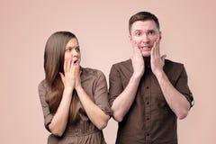 Сотрясены женщина и человек в коричневых одеждах, изумленный, удивленный стоковые фото