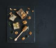 Сот, грецкие орехи и ковш меда на черном шифере Стоковые Изображения