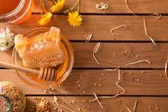 Сот с цветнем меда и пчелы на деревянной столешнице Стоковые Изображения