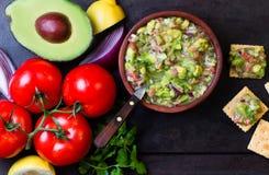 Соус гуакамоле латино-американский мексиканский в шаре и ингридиентах глины стоковое фото rf