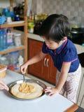 Соус пиццы маленького азиатского ребёнка spreding над тестом пиццы стоковое изображение