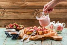Соус руки лить cream от стеклянного опарника на домодельной клубнике c Стоковое Фото