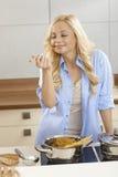 Соус спагетти дегустации молодой женщины в кухне Стоковая Фотография RF