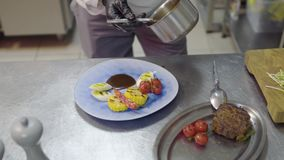 Соус шеф-повара лить на плите с мясом приготовления на гриле, мозолью, томатами вишни, лимонным соргом и перцем chili лежа там видеоматериал