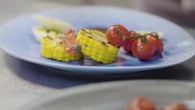 Соус шеф-повара лить на плите с мясом приготовления на гриле, мозолью, томатами вишни, лимонным соргом и перцем chili лежа там сток-видео