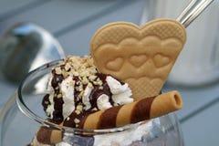 Соус шоколада на сливк с фундуком брызгает и waffle в форме сердца, конце вверх стоковые изображения