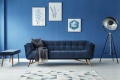 Софа, лампа и footstool в комнате бесплатная иллюстрация