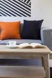 Софа и подушки в живущей комнате с кофе и книгой на деревянном столе Стоковое Фото