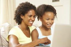 софа мати компьтер-книжки дочи домашняя используя Стоковые Изображения