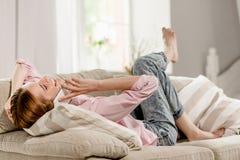 Софа маленькой девочки лежа говоря на сотовом телефоне Стоковая Фотография RF