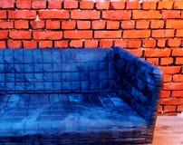 Софа слойки плюша голубая на стиле backgrund кирпича винтажном промышленном Стоковая Фотография RF
