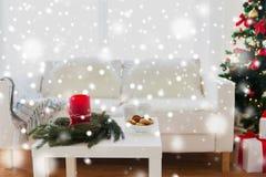 Софа, таблица и рождественская елка с подарками дома стоковые фотографии rf