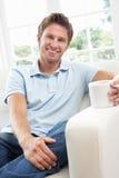 софа человека ho кофе выпивая ослабляя сидя Стоковое Изображение RF