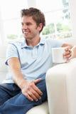 софа человека ho кофе выпивая ослабляя сидя Стоковое Фото