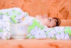 софа девушки домашняя лежа Стоковое фото RF