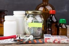 Сохраняя деньги для страхования здравоохранения - стекло, стетоскоп, таблетки и бутылки денег стоковые изображения
