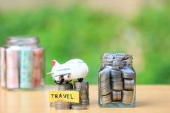 Сохраняя планирование для бюджета перемещения концепции праздника, финансовый, стога денег монеток в стеклянной бутылке и самолет стоковые фотографии rf