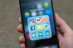 Социальные значки показанные на iPhone Яблока, некоторые значки приложения средств массовой информации с уведомлениями стоковая фотография