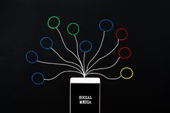 Социальные средства массовой информации и концепция связи, smartphone с круглой резинкой с сочинительством руки социального значк стоковое фото