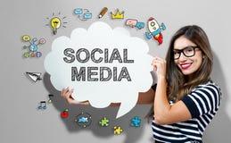 Социальные средства массовой информации отправляют СМС при женщина держа пузырь речи стоковое фото rf
