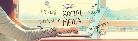 Социальные средства массовой информации при женщина работая на компьтер-книжке стоковое изображение rf