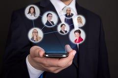 Социальная концепция сети - современный умный телефон в руке бизнесмена