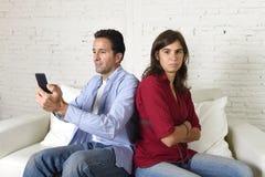 Социальный человек наркомана сети используя мобильный телефон игнорируя осадку жены или подруги и сердитое Стоковая Фотография