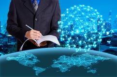 Сочинительство бизнесмена на книге с виртуальным цифровым глобусом на nig Стоковая Фотография RF