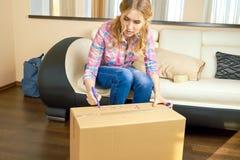 Сочинительство девушки на картонной коробке Стоковые Изображения