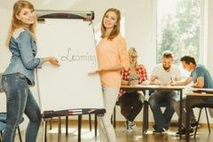 Сочинительство девушки студента уча слово на whiteboard Стоковое Фото