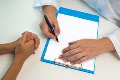 Сочинительство доктора на доске сзажимом для бумаги для пациента Медицинская концепция назначения стоковая фотография rf