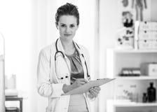 Сочинительство женщины врача в доске сзажимом для бумаги Стоковые Изображения