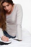 Сочинительство женщины в ее дневнике стоковые фото