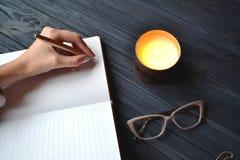 Сочинительство женщины в тетради Стильные объекты на деревянном столе Атмосфера ослабляет Стоковое Изображение