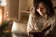 Сочинительство женщины на sketchbook Стоковое Фото