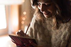 Сочинительство женщины на sketchbook Стоковая Фотография