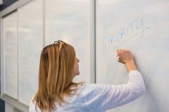 Сочинительство женщины на whiteboard в встрече Стоковая Фотография