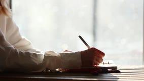 Сочинительство женщины с ручкой что-то внутри к тетради сток-видео