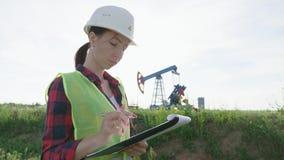 Сочинительство инженера женщины на доске сзажимом для бумаги в месторождении нефти Женские нося белые шлем и рабочая одежда Промы сток-видео