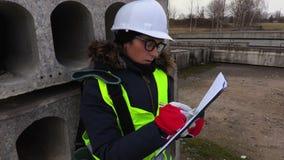 Сочинительство инженера женщины около бетонных плит акции видеоматериалы