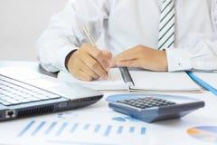 сочинительство и память бизнесмена на тетради и калькуляторе на плате Стоковое Фото