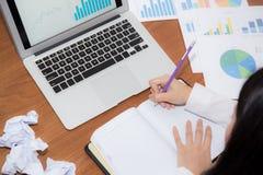 Сочинительство коммерсантки на тетради на столе, азиатской женщине с не идеей с компьтер-книжкой анализа диаграммы и скомканной б Стоковое фото RF
