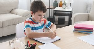 Сочинительство мальчика в тетради и бумаге видеоматериал