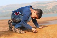 Сочинительство мальчика на земле с его пальцем на ghat Tamihini, Пуне стоковые фото