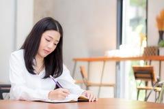 Сочинительство молодой женщины красивого дела азиатское на тетради на таблице Стоковое Изображение