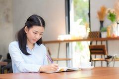 Сочинительство молодой женщины красивого дела азиатское на тетради на таблице Стоковая Фотография RF