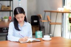Сочинительство молодой женщины красивого дела азиатское на тетради на таблице Стоковые Фото