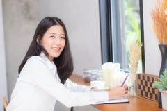 Сочинительство молодой женщины красивого дела азиатское на тетради на tabl Стоковые Изображения