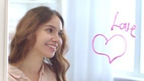 Сочинительство молодой женщины любовью слова губной помады на зеркале с сердцем в bathroom акции видеоматериалы